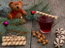 Fir-tree branch, toy bear, tea, baking and nutlets Royalty Free Stock Images