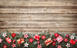 Fir tree branches with advent calendar stars and gift boxes. On old wooden board Stock Photos