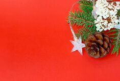 Fir tree branches with Christmas decoration on red background. Free copy space.