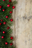 Fir tree branches decorated with red christmas balls as border o Stock Photos