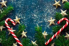 Fir tree branches decorative golden star ornaments candy canes snow dust on dark blue turquoise backdrop. Christmas New Year stock photography