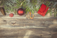 Fir tree branches with gift box, candies, cone and christmas ball on wooden background Stock Images