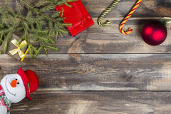 Fir tree branches with gift box, cane candies, christmas ball and funny snowman on wooden background Royalty Free Stock Images