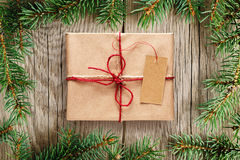 Fir tree branches and gift box with tag Royalty Free Stock Image