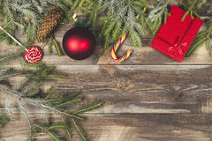 Fir tree branches with gift boxes, candies, cone and christmas ball on wooden background Stock Photos