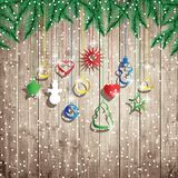 Fir tree branches and hanging toys on the wooden board background. Christmas vector illustration Stock Images