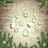Fir tree branches and hanging toys on the wooden board background. Stock Image