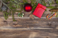 Fir tree branches with red gift boxes, candy cane, cones and christmas ball on wooden background Royalty Free Stock Images