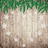 Fir tree branches and snowflakes on the wooden board. Royalty Free Stock Photo