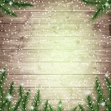 Fir tree branches and snowflakes on the wooden board. Stock Photos