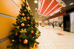 Fir-tree covered by Christmas ornaments in store. Fir-tree densely covered by Christmas ornaments in shopping centre corridor Royalty Free Stock Image