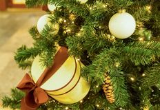 Fir-tree decorated with a glowing garland with light bulbs, a white shiny Christmas ball and a round cream box. Tied with a chocolate ribbon stock photo