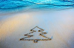 Fir tree drawing on the sand near the sea . Christmas background. royalty free stock photo