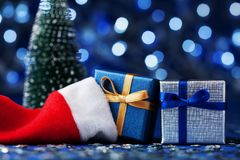 Fir tree, santa hat and christmas gift box or present on blue bokeh background. Magic holiday greeting card. Stock Photography