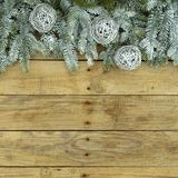 Fir tree with silver glitter balls on wooden natural rough background. Christmas postcard in green and white. Fir tree with silver glitter balls on wooden stock photo