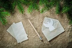 Fir tree twig envelope paper angel pencil on bagging surface Royalty Free Stock Images