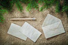 Fir tree twig envelope paper pencil on bagging background Royalty Free Stock Photo