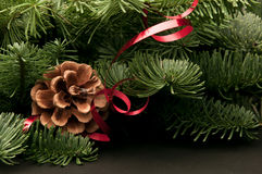 Fir-tree twigs with cones and a red ribbon Royalty Free Stock Photo