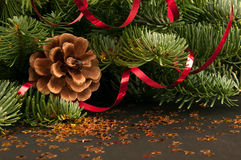 Fir-tree twigs with cones and a red ribbon Royalty Free Stock Photography