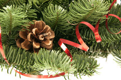 Fir-tree twigs with cones and a red ribbon Stock Images