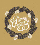 Fir-tree wreath with cones and stylish calligraphy Merry Christmas on the cardboard. Traditional green Christmas decoration. Fir-tree wreath with cones and Royalty Free Stock Photography