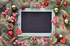 Fir twig decorated with baubles, berries and stars, black-board, royalty free stock photo