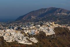 Fira和先知伊莱亚斯峰顶,圣托里尼海岛,锡拉,希腊镇的全景  免版税图库摄影