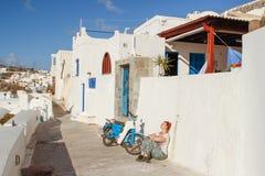 Fira有白色房子和一个白游人的镇街道戴眼镜坐与她回到墙壁在摩托车旁边 库存图片