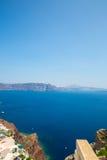 Fira镇-圣托里尼海岛,克利特希腊看法  导致下来与清楚的蓝天的美丽的海湾的白色具体楼梯和 库存照片