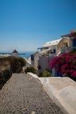 Fira镇-圣托里尼海岛,克利特,希腊看法 导致下来与清楚的蓝天的美丽的海湾的白色具体楼梯和 库存照片