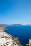 Fira镇-圣托里尼海岛,克利特,希腊看法 导致下来与清楚的蓝天的美丽的海湾的白色具体楼梯和 免版税图库摄影