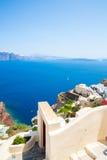 Fira镇-圣托里尼海岛,克利特,希腊看法 导致下来与清楚的蓝天的美丽的海湾的白色具体楼梯和 库存图片