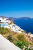 Fira镇-圣托里尼海岛,克利特,希腊看法 导致下来与清楚的蓝天的美丽的海湾的白色具体楼梯 库存图片