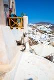 Fira镇-圣托里尼海岛,克利特,希腊看法 导致下来与清楚的蓝天的美丽的海湾的白色具体楼梯 库存照片