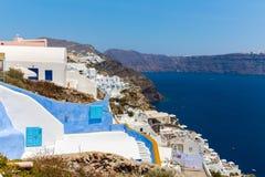Fira镇-圣托里尼海岛,克利特,希腊看法。导致下来与清楚的蓝天的美丽的海湾的白色具体楼梯 库存照片