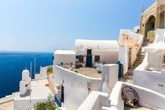 Fira镇-圣托里尼海岛,克利特,希腊看法。导致下来与清楚的蓝天的美丽的海湾的白色具体楼梯 库存图片