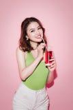 Fira den asiatiska kvinnan som dricker den röda softdrinken Arkivbilder
