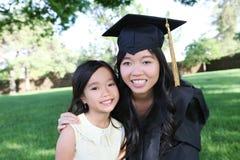 fira dotteravläggande av examenmoder Arkivfoto