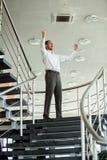 fira framgång Spännande ung affärsman som håller armar lyftta och uttrycker positivity, medan stå i regeringsställning royaltyfri fotografi