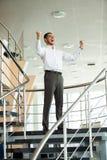 fira framgång Spännande ung affärsman som håller armar lyftta och uttrycker positivity, medan stå i regeringsställning arkivfoton