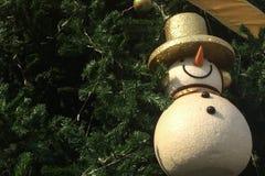 Fira jul och bakgrundsbegreppet för nytt år, den glänsande prydnadsnögubben med den guld- hatten och det guld- bandet på hörnet Arkivbilder