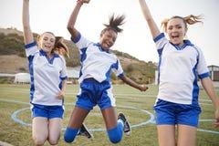 Fira kvinnliga högstadiumstudenter som spelar i fotbolllag royaltyfri bild