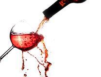 Fira med rött vin på exponeringsglasfärgstänk som isoleras på vit arkivbilder