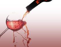 Fira med rött vin på exponeringsglasfärgstänk som isoleras på vit royaltyfri bild
