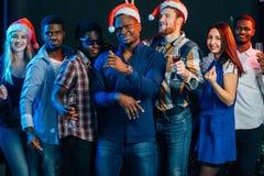 Fira nytt år tillsammans Grupp av härliga ungdomari jultomtenhattar royaltyfri foto