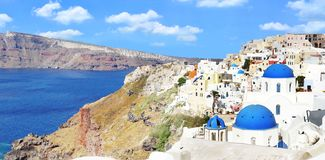 Fira, Santorini, Greece. Panoramic picture of the scenic blue and white houses, sea, clouds and sky in Fira, Santorini, Greece showing the red volcanic soil of royalty free stock images