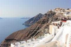 Fira, Santorini, Greece - September 17, 2016: Tourists travel to the picturesque village Fria on Santorini Island, Greece. Stock Image