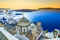 Fira, Santorini, with white village, cobbled paths, greek orthodox blue church and sunset over caldera. Cyclades, Greece stock photography