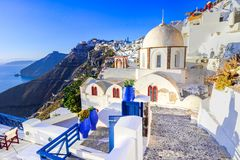 Fira, Santorini, with white village, cobbled paths, greek orthodox blue church and sunset over caldera. Cyclades, Greece stock image
