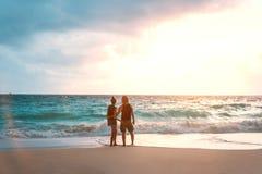 Fira smekmånad omfamna för par den förälskade och tyckande om havsikten på stranden Arkivbild